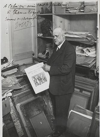 """Ambroise Vollard (1868-1939) tenant à la main le prospectus des """"Réincarnations du Père Ubu"""", livre illustré par Georges Rouault (1871-1958) photographié au 28 rue de Martignac, Fonds Vollard, vers 1932. © ADAGP, Paris /Bonney Therese (dite), Bonney Mabel (1894-1978). © Droit Etat / Therese Bonney. Localisation : Paris, musée d'Orsay. Photo © Musée d'Orsay, Dist. RMN-Grand Palais / Patrice Schmidt."""