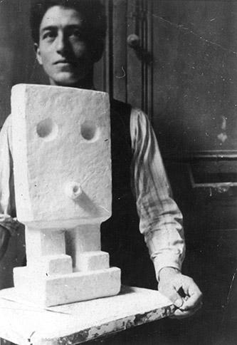 Alberto Giacometti et Petit homme (1926-1927) en plâtre. Photo : anonyme, n. d. Archives de la Fondation Giacometti, Paris. © Succession Alberto Giacometti (Fondation Giacometti, Paris +ADAGP, Paris) 2020.