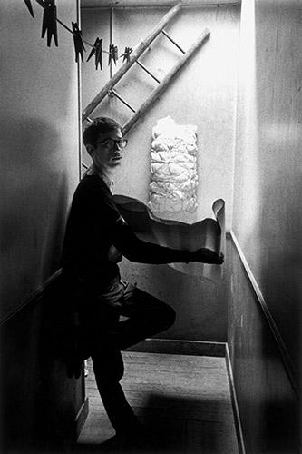 Christo dans le couloir menant à son atelier, 14, rue de Saint-Senoch, Paris, 17e arr., 1962. © Christo 1962. © Enzo Sellerio - Olivia et Antonio Sellerio ayants-droit de Enzo Sellerio.