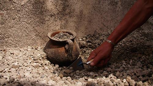 Un récipient pour la cuisson des aliments émerge du lapilli lors de l'excavation, Ier siècle après J.-C.. Pompéi, Royal V. © GEDEON Programmes.