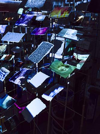 Sarah Sze, Slice, 2018. Prototype dans le cadre de l'exposition Night Into Day à la Fondation Cartier. Matériaux mixtes, bois, acier inoxydable, acrylique, vidéoprojecteurs, impressions pigmentaires, céramique et scotch. Dimensions variables. © Sarah Sze Photo © Sarah Sze Studio.