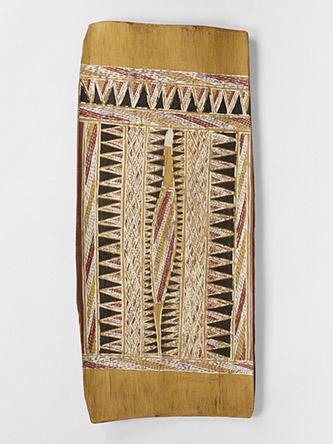 """Tom Djawa, groupe Gupapuyngu, moitié Yirritya, 1905 – 1983, Peinture sur écorce, 1963. N° inventaire : 72.1964.9.10. """"Mundukul"""", serpent marin bigarré ; Les nuages qu'il a créés en soufflant l'eau avalée, sont représentés par des triangles. Retranscription exacte de peinture corporelle """"Yirritya"""". Ecorce, pigments blanc, noir, rouge, jaune et rouge-brun, 55 x 24,5 x 2,5 cm. © musée du quai Branly - Jacques Chirac, photo Pauline Guyon. © ADAGP, Paris, 2021. Photographe : Pauline Guyon."""