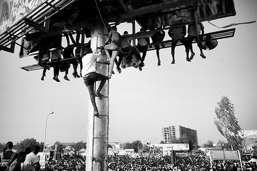 Ahmed Ano. Des civils escaladent d'énormes panneaux publicitaires pour crier «Liberté, paix et justice». Sit-in, quartier général militaire, Khartoum, 19 avril 2019.