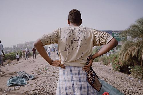 Muhammad Salah. Un manifestant dont l'inscription au dos de sa chemise signifie «Un révolutionnaire de Kalakla, que la dictature tombe!»; il se tient sur la ligne ferroviaire centrale de Khartoum qui faisait partie de la zone de sit-in du QG de l'armée. Khartoum, Soudan, 13 avril 2019.