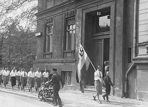 Des étudiants allemands de la Deutsche Hochschule fuür Leibesübungen (DHfL) [Université allemande d'éducation physique] défilent devant l'Institut de sexologie avant le pillage du bâtiment. Berlin. 6 mai 1933. Coll. United States Holocaust Memorial Museum (Washington), courtesy of National Archives and Records Administration, College Park.
