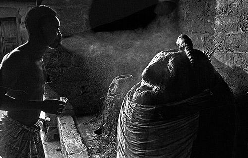 Catherine De Clippel, Un assistant du prêtre Séwavi vaporise de l'alcool de palme sur le vodou Djagli à Séko. Togo, 1989. © Catherine De Clippel.